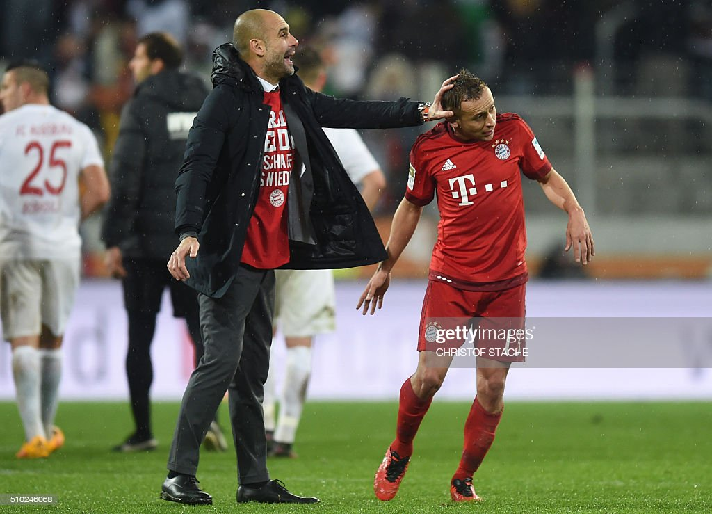Bayern Munich's Spanish headcoach Pep Guardiola (R) jokes with Bayern Munich's Brazilian defender Rafinha (R) after the German first division Bundesliga football match of FC Augsburg vs FC Bayern Munich in Augsburg, southern Germany, on February 14, 2016. / AFP / CHRISTOF STACHE /