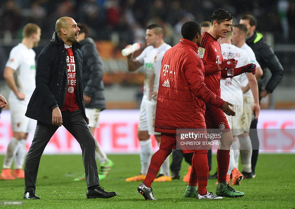 Bayern Munich's Spanish headcoach Pep Guardiola jokes with Bayern Munich's Brazilian midfielder Douglas Costa and Bayern Munich's Polish striker Robert Lewandowski after the German first division Bundesliga football match of FC Augsburg vs FC Bayern Munich in Augsburg, southern Germany, on February 14, 2016. / AFP / CHRISTOF STACHE /
