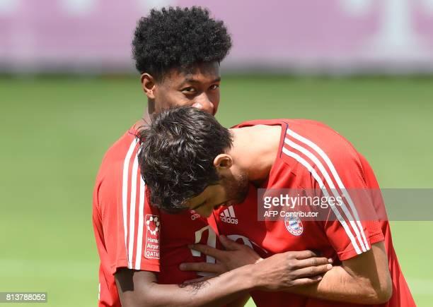 Bayern Munich's Spanish midfielder Javier Martinez and Bayern Munich's Austrian defender David Alaba joke as they attend a training session of German...