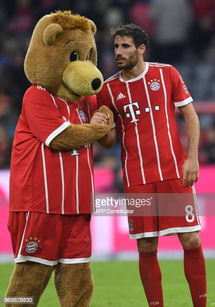 Bayern Munich's Spanish midfielder Javier Martinez shakes hands with his club's mascot Berni after the German first division Bundesliga football...