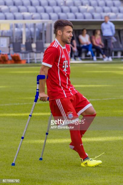 Bayern Munich's Spanish midfielder Juan Bernat hobbels on crutches to the team photo session of FC Bayern Munich in the southern German city of...