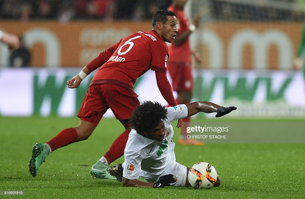 Bayern Munich's Spanish midfielder Thiago Alcantara (L) and AAugsburg's Brazil midfielder Caiuby vie for the ball during the German first division Bundesliga football match of FC Augsburg vs FC Bayern Munich in Augsburg, southern Germany, on February 14, 2016. / AFP / CHRISTOF STACHE /