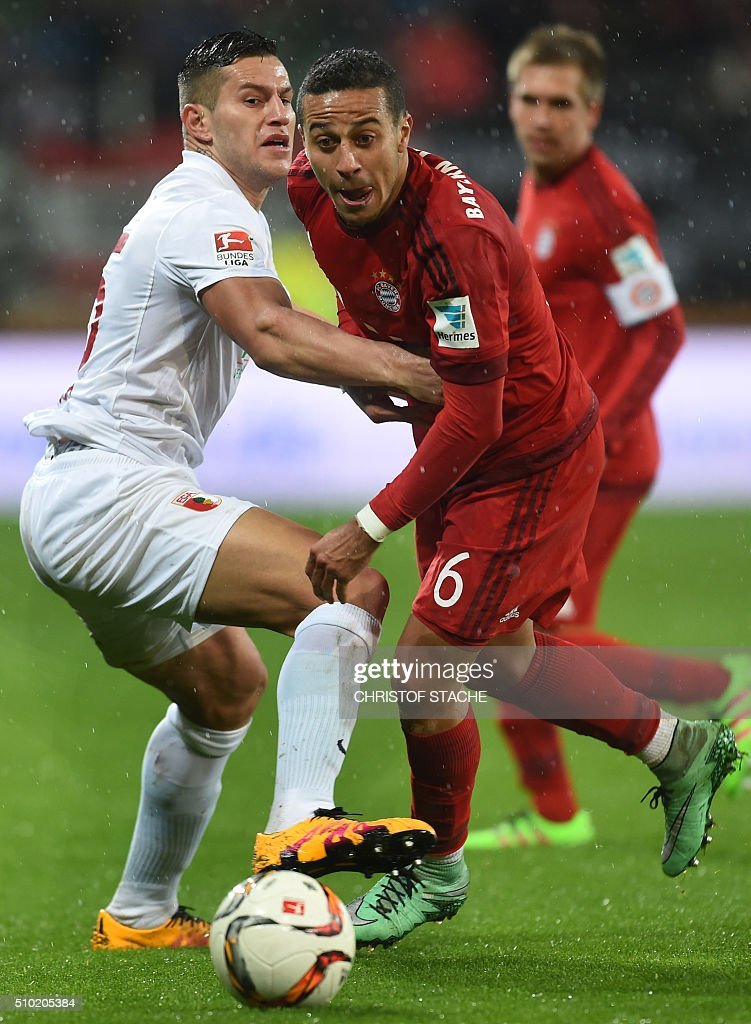 Bayern Munich's Spanish midfielder Thiago Alcantara (R) and Augsburg's Argentinian striker Raul Bobadilla vie for the ball during the German first division Bundesliga football match of FC Augsburg vs FC Bayern Munich in Augsburg, southern Germany, on February 14, 2016. / AFP / CHRISTOF STACHE /