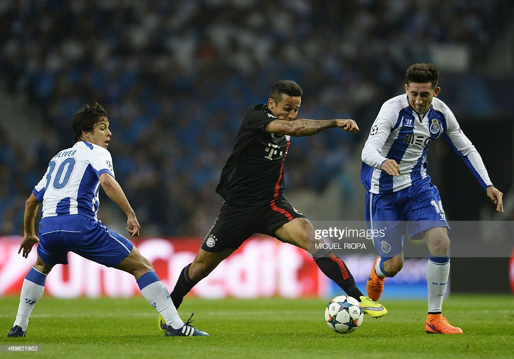 Bayern Munich's Spanish midfielder Thiago Alcantara (C) vies with Porto's Spanish midfielder Oliver Torres (L) and Mexican midfielder Hector Herrera during the UEFA Champions League quarter final football match FC Porto vs FC Bayern Munich at the at the Dragao stadium in Porto on April 15, 2015.