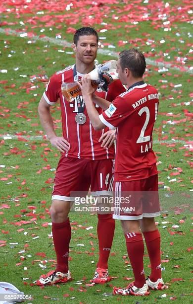 Bayern Munich's Spanish midfielder Xabi Alonso and Bayern Munich's defender Philipp Lahm celebrate with beer after the German first division...