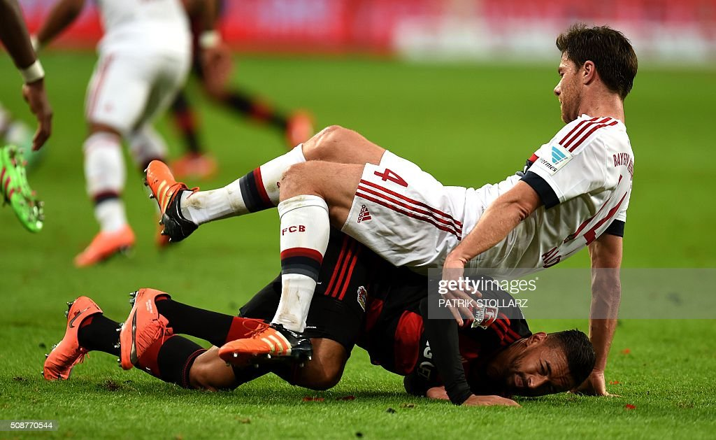 Bayern Munich's Spanish midfielder Xabi Alonso and Leverkusen's midfielder Karim Bellarabi vie for the ball during the German first division Bundesliga football match of Bayer 04 Leverkusen v Bayern Munich in Leverkusen, western Germany, on February 6, 2016. / AFP / PATRIK STOLLARZ /