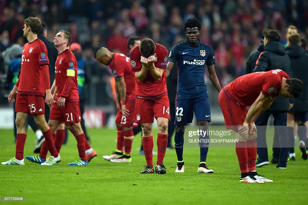 Bayern Munich's Spanish midfielder Xabi Alonso (C) and teammates react after the UEFA Champions League semi-final, second-leg football match between FC Bayern Munich and Atletico Madrid in Munich, southern Germany, on May 3, 2016. / AFP / GUENTER