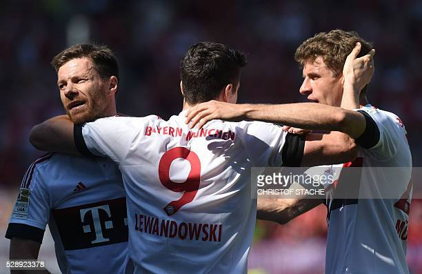 Bayern Munich's Spanish midfielder Xabi Alonso Bayern Munich's Polish striker Robert Lewandowski and Bayern Munich's striker Thomas Mueller celebrate...