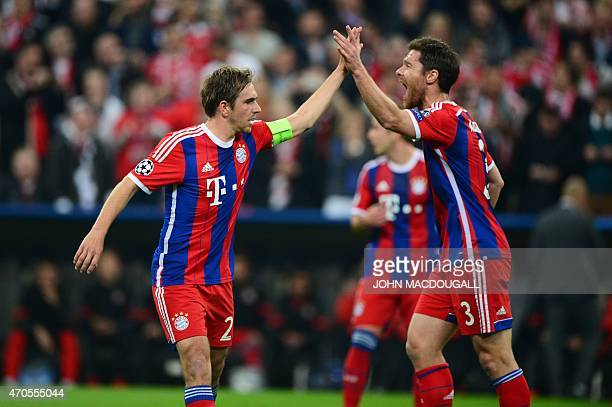 Bayern Munich's Spanish midfielder Xabi Alonso celebrates with Bayern Munich's defender Philipp Lahm during the UEFA Champions League secondleg...