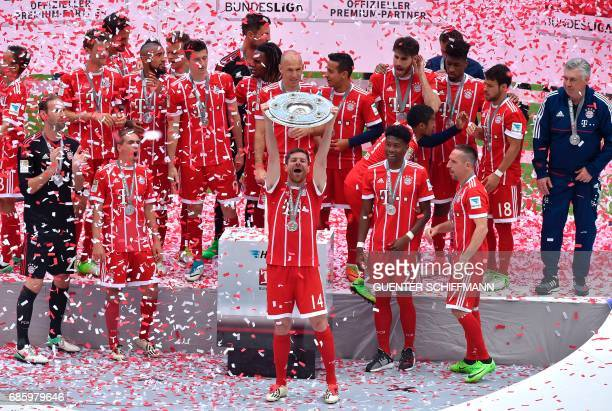 Bayern Munich's Spanish midfielder Xabi Alonso holds the trophy as Bayern Munich's players celebrate after the German first division Bundesliga...