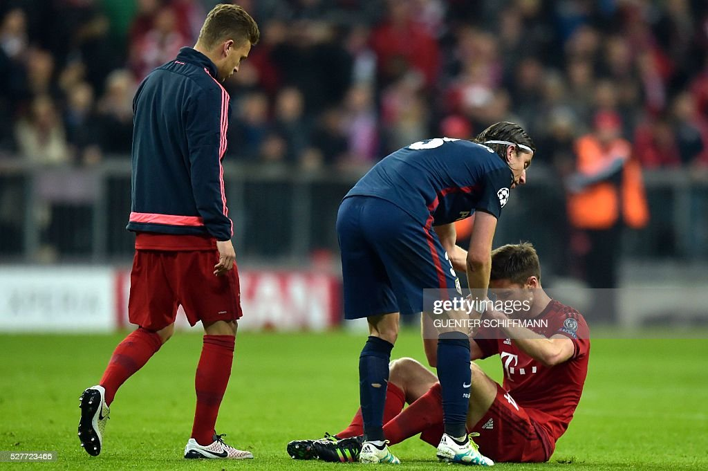 Bayern Munich's Spanish midfielder Xabi Alonso (R) is comforted by Atletico Madrid's Brazilian defender Filipe Luis (2ndR) after the UEFA Champions League semi-final, second-leg football match between FC Bayern Munich and Atletico Madrid in Munich, southern Germany, on May 3, 2016. / AFP / GUENTER