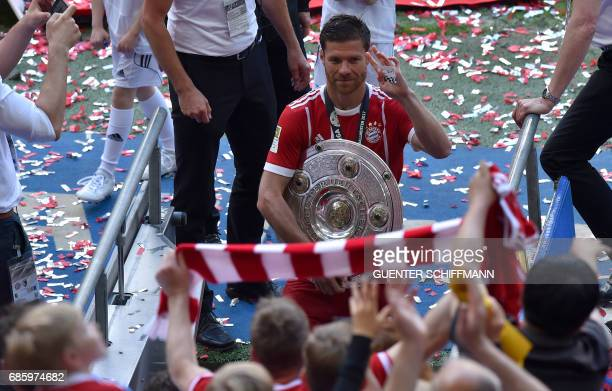Bayern Munich's Spanish midfielder Xabi Alonso leaves the pitch with the trophy after the German First division Bundesliga football match Bayern...