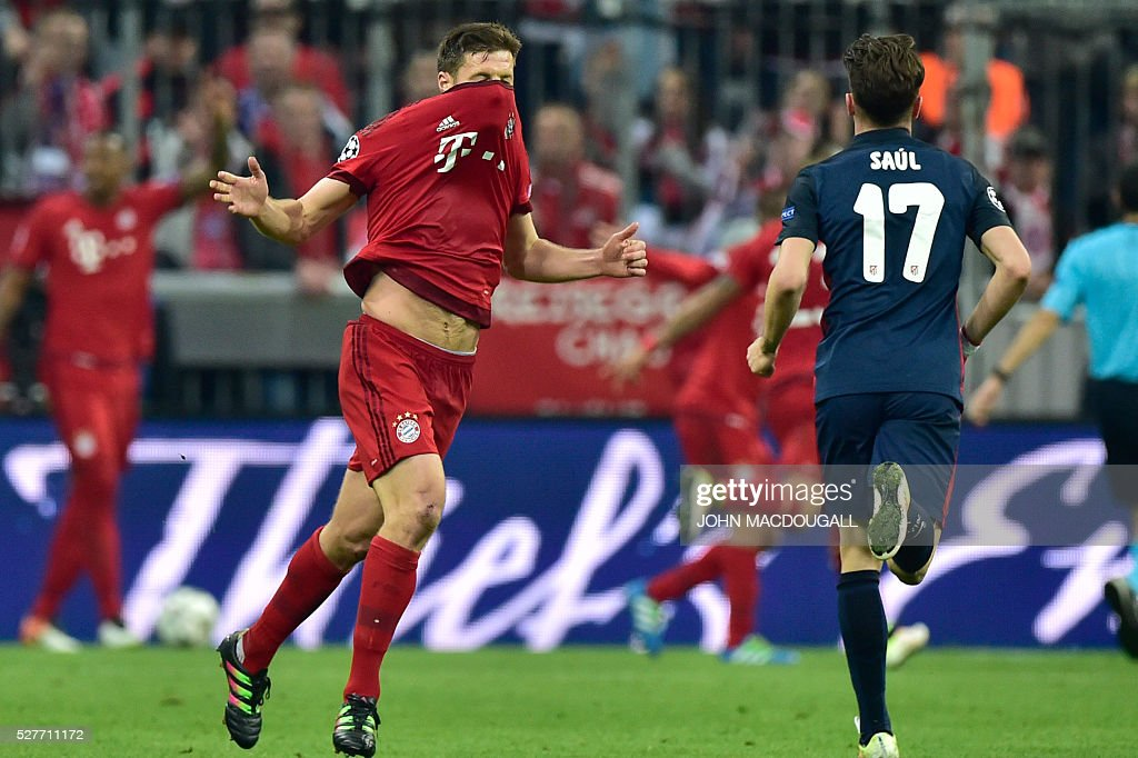 Bayern Munich's Spanish midfielder Xabi Alonso (l) reacts during the UEFA Champions League semi-final, second-leg football match between FC Bayern Munich and Atletico Madrid in Munich, southern Germany, on May 3, 2016. / AFP / John MACDOUGALL