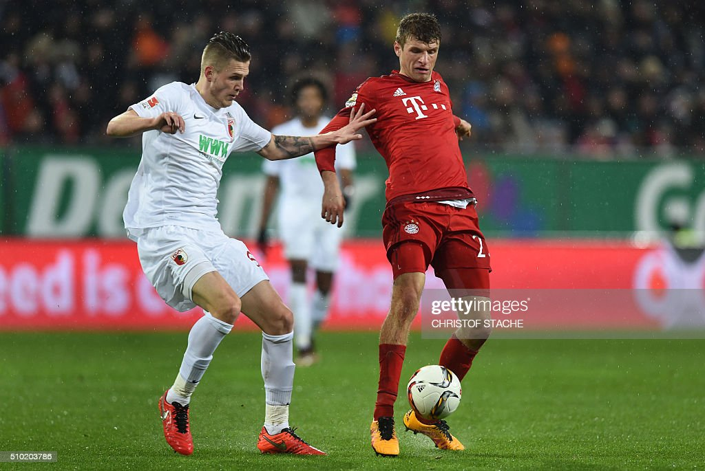 Bayern Munich's striker Thomas Mueller (R) and Augsburg's Dutch defender Jeffrey Gouweleeuw vie for the ball during the German first division Bundesliga football match of FC Augsburg vs FC Bayern Munich in Augsburg, southern Germany, on February 14, 2016. / AFP / CHRISTOF STACHE /