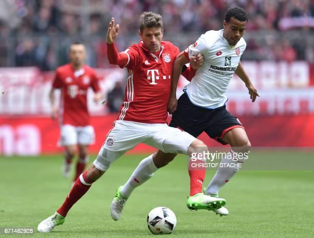 Bayern Munich's striker Thomas Mueller and Mainz' Swedish midfielder Robin Quaison vie for the ball during the German First division Bundesliga...