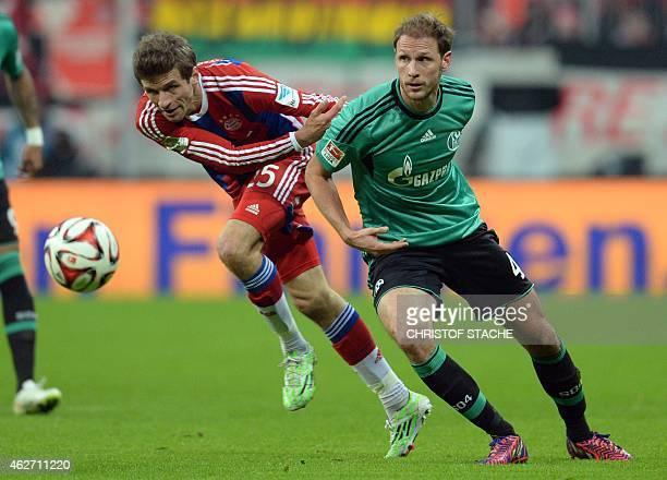 Bayern Munich's striker Thomas Mueller and Schalke's defender Benedikt Hoewedes vie for the ball during the German first division Bundesliga football...