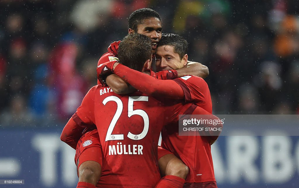 Bayern Munich's striker Thomas Mueller, Bayern Munich's Brazilian midfielder Douglas Costa and Bayern Munich's Polish striker Robert Lewandowski celebrate after the third goal for Munich during the German first division Bundesliga football match of FC Augsburg vs FC Bayern Munich in Augsburg, southern Germany, on February 14, 2016. / AFP / CHRISTOF STACHE /