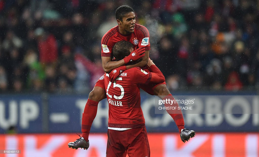 Bayern Munich's striker Thomas Mueller celebrates scoring the 0-3 goal with Bayern Munich's Brazilian midfielder Douglas Costa during the German first division Bundesliga football match of FC Augsburg vs FC Bayern Munich in Augsburg, southern Germany, on February 14, 2016. / AFP / CHRISTOF STACHE /