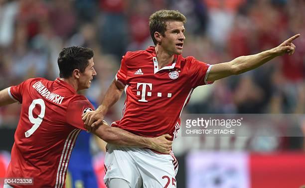 Bayern Munich's striker Thomas Mueller celebrates scoring the 20 goal with his teammate Bayern Munich's Polish striker Robert Lewandowski during the...