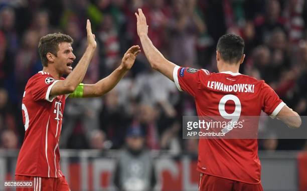 Bayern Munich's striker Thomas Mueller celebrates scoring the opening goal with Bayern Munich's Polish striker Robert Lewandowski during the...