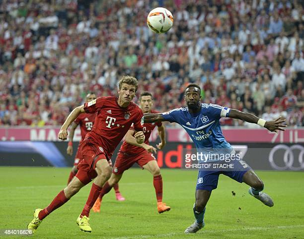 Bayern Munich's striker Thomas Mueller goes to head in the 30 goal for Munich past Hamburg's Swiss defender Johan Djourou during the German first...