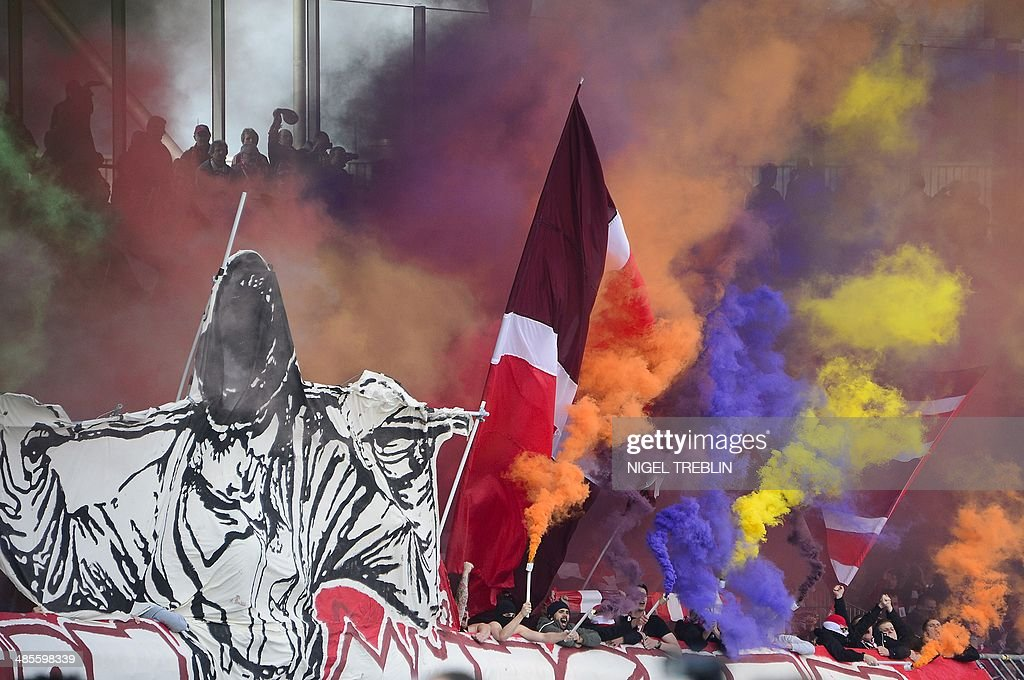Bayern Munich's supporters handle fireworks ahead of the German first division Bundesliga football match Eintracht Braunschweig vs FC Bayern Munich in Braunschweig, central Germany, on April 19, 2014. AFP PHOTO / NIGEL TREBLIN
