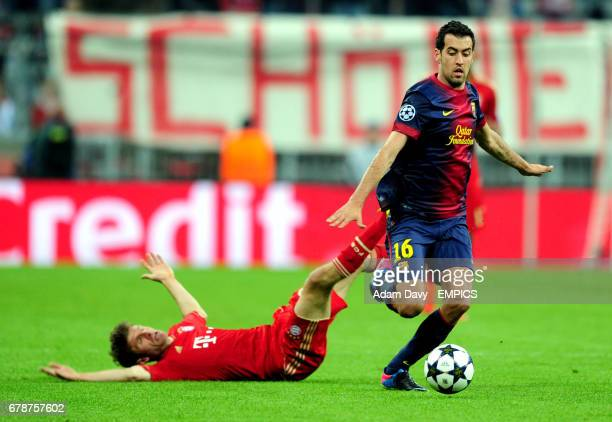 Bayern Munich's Thomas Muller and Barcelona's Sergio Busquets battle for the ball