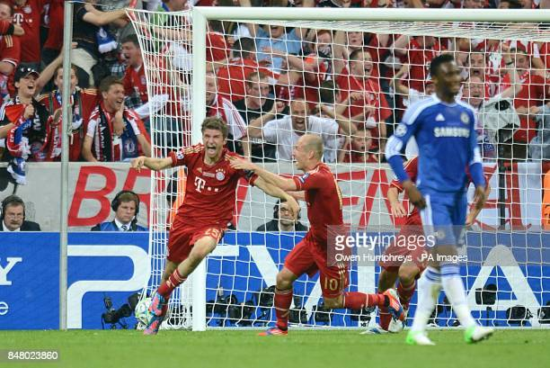 Bayern Munich's Thomas Muller celebrates scoring their first goal of the game with teammate Arjen Robben as Chelsea's Mikel stands dejected