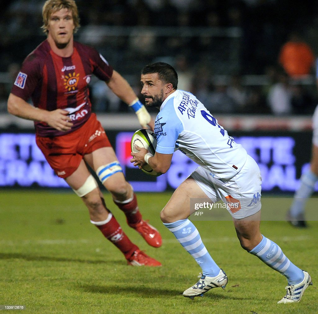 Bayonne's French fly half Cédric Garcia runs with the ball in front of Montpellier's Remy Martin during their French Top 14 rugby union match Aviron...