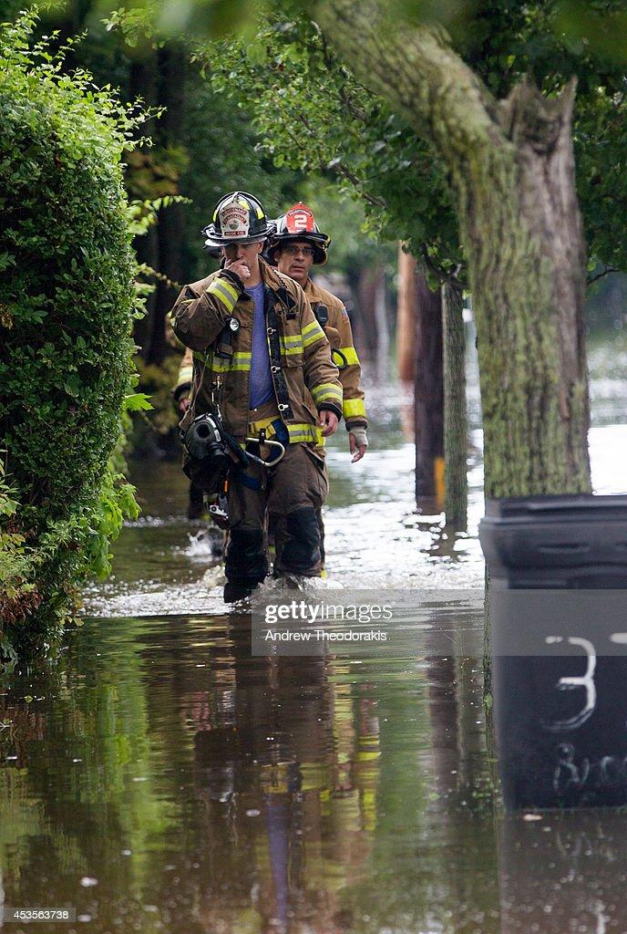 Bayshore Fire Fighters walk along Brooke Ave following heavy rains and flash flooding on August 13, 2014 in Bayshore, New York. The south shore of Long Island along with the tri-state region saw record setting rain that caused roads to flood entrapping some motorists.