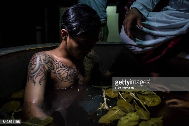 Bayu a recovering drug addict sits in a hot water herbal bath as theatment by the head of rehabilitation centre Ustad Ahmad Ischsan Maulana at the...