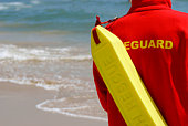 A lifeguard complete with rescue float monitors their beach