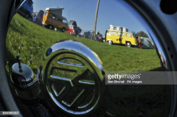 VW Baywindow Type 2 Transporters are reflected in a VW chrome hubcap at Vanfest festival in the Three Counties Showground Malvern where thousands of...