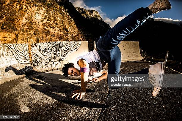 B-boy going into  shoulder spin while breakdancing on a road