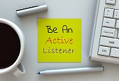 Be An Active Listener, message on note paper, computer and coffee on table
