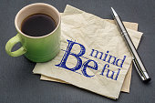 Be mindful  - handwriting on a napkin with cup of coffee against gray slate stone background