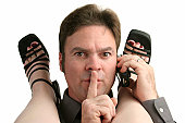 A man having an office affair answering his cell phone and quieting his partner.