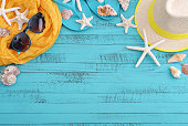 Beach accessories with sea shells on blue wooden board