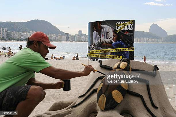 A beach artist gives the final touches to a sand sculpture of the Chagas disease's vector the 'assassin bug' during a demonstration July 9 2009 at...