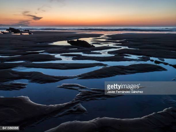 A beach at sunset. Shapes of water and sand with the tide.