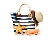 Beach bag with towel, starfish, straw hat and sunglasses isolated on white