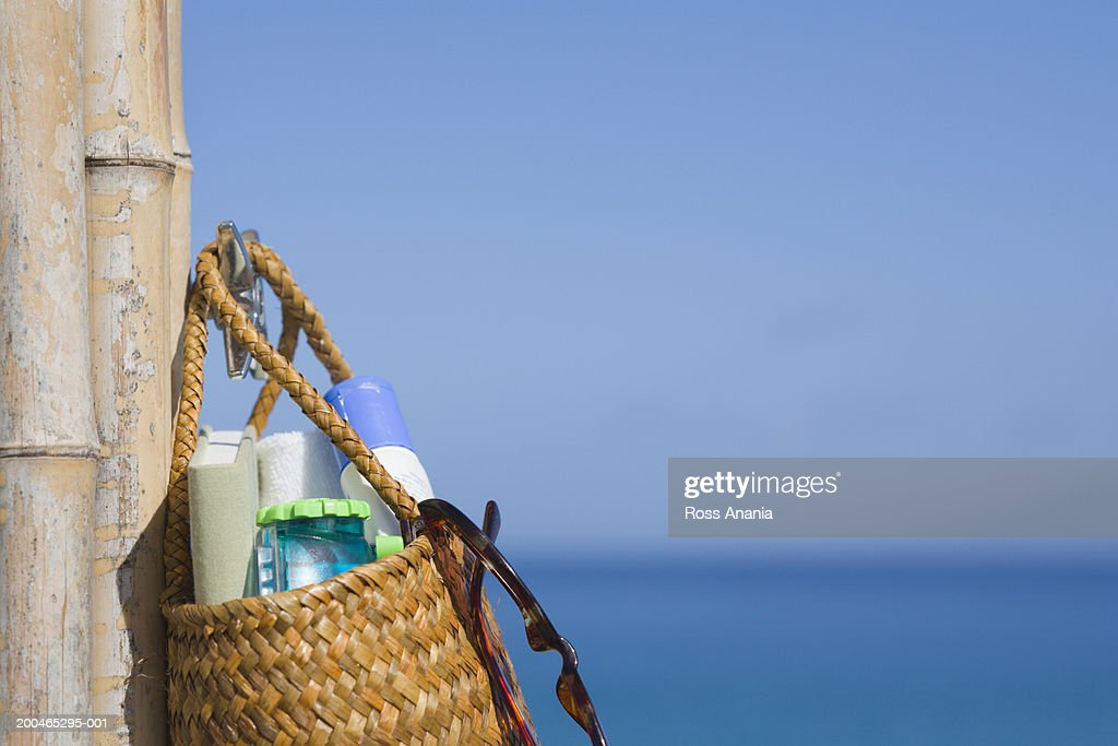 Beach bag hanging on bamboo post by coast, close-up : Stock Photo