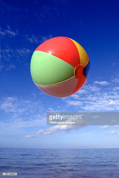Beach ball airborne over ocean