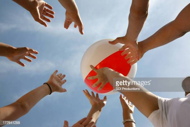 Beach Ball Being Boundced Around By Hands In The Sun