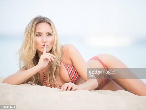 Beauté sur la plage avec son doigt sur les lèvres