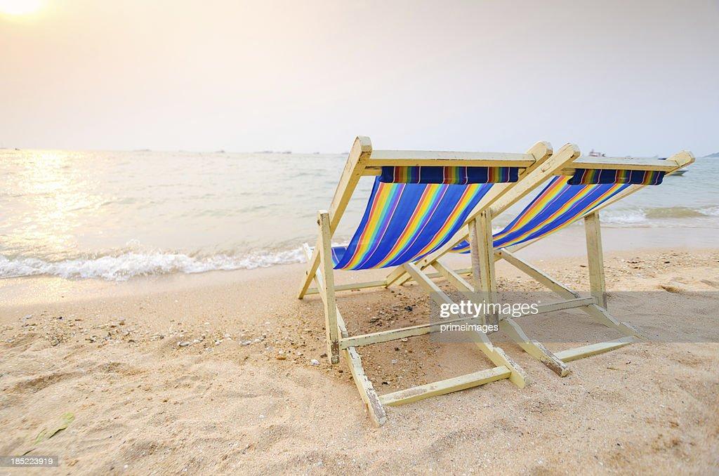 Beach chairs on perfect tropical white sand beach.