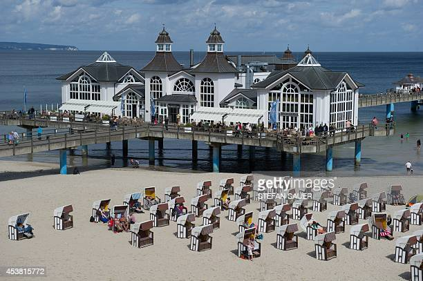 Beach chairs stand in front of the pier of Sellin on the Baltic Sea island of Ruegen northeastern Germany on August 19 2014 Air temperature in the...