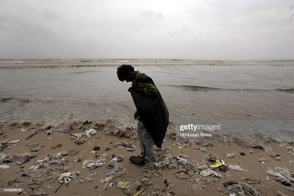 A beach comber skims around Juhu Beach in the wee hours of the morning on July 20, 2005 in Mumbai, India.