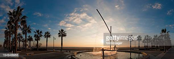 Beach fountain sunrise Mediterranean palm tree promenade panorama Valencia Spain