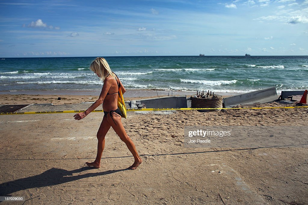 A beach goer walks past where the ocean now laps up against route A-1-A making parts of it impassable to vehicles on November 27, 2012 in Fort Lauderdale, Florida. The beach was eroded away last month when Hurricane Sandy passed by to the east and now City officials are saying that the damage may preview what rising sea levels can mean for coastal communities throughout South Florida. Climate scientists predict sea levels in South Florida will rise by 1 foot by 2070, 2 feet by 2115, and 3 feet by 2150.